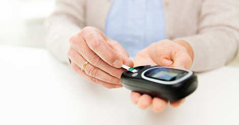 Woman with glucometer checking blood sugar