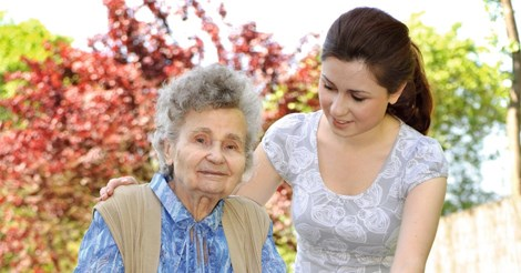 Carer assisting elderly woman