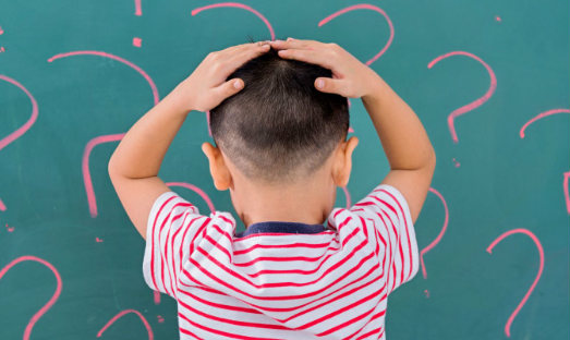 A small child with his back turned and both hands on his head, in front of a blackboard with question marks drawn on it