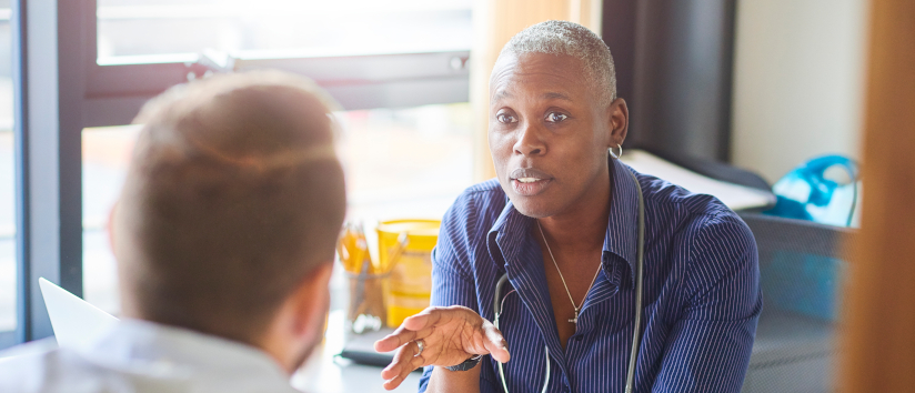 Female GP speaking to male patient in GP surgery