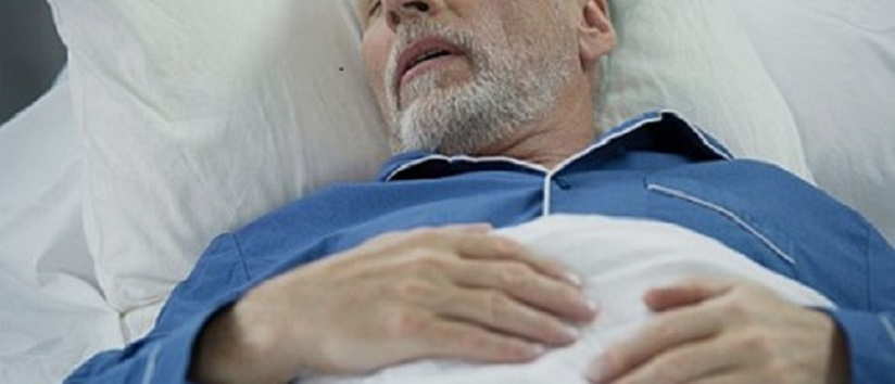 older man asleep in bed
